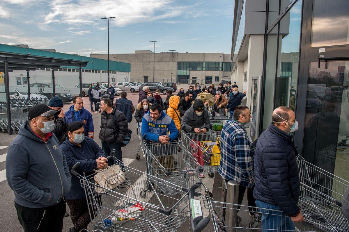 Ludzie w maskach w kolejce do sklepu w mieście Casalpusterlengo